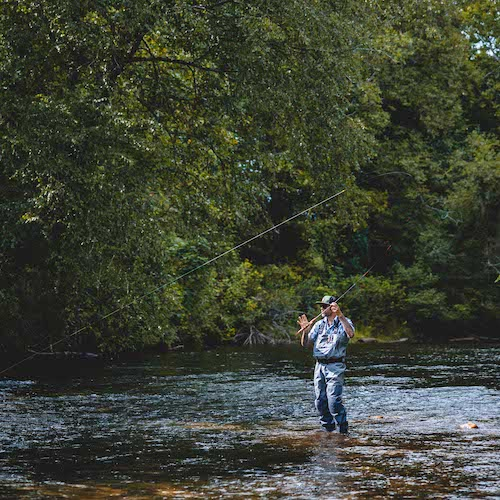 man fly fishing in a stream